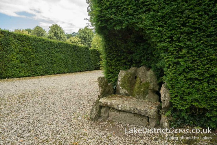 A tiny stone seat cut into the hedge at Levens Hall